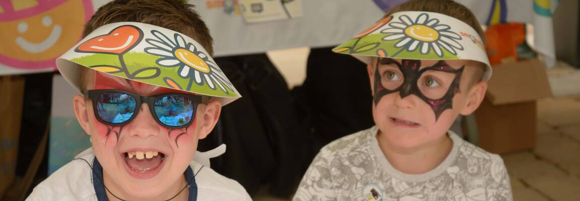 Two boys with painted faces smile at the camera